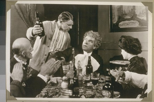 """Speech, speech!"" shouted Marcus""... Page 119. [Jean Hersholt, with bottle; Gibson Gowland, center; Zasu Pitts, right.]"