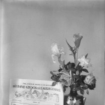 "View of a floral arrangement in front of a sign that reads: "" The Paper with a Purpose: Livestock and Dairy Journal."""