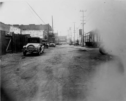 Olvera Street looking north, Avial Adobe on right, old cars parked on west side of street, Sepulveda House has large pole in front of it, Tool and Die shop at north end