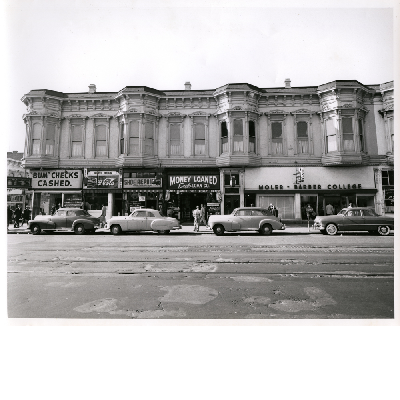 West side of Broadway between 9th and 10th Streets in downtown Oakland, California. White Onion, Eagle Loan Co., Moler Barber College in view