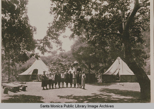 A group of young women campers join together for this photo in front of large tents at Institute Camp, Temescal Canyon, Calif