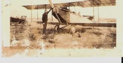 Sam Huck at propeller of biplane, about 1920s