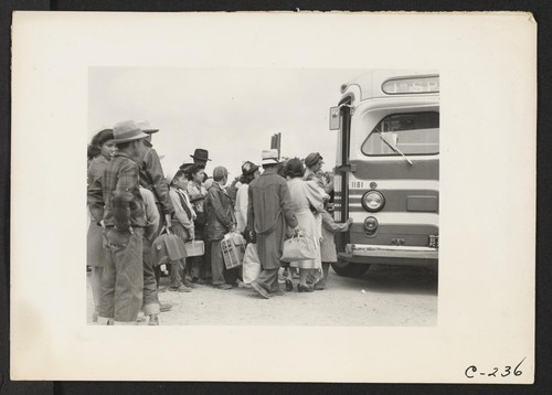 The bus has just arrived and these farm families of Japanese ancestry are being kept intact enroute to the Assembly Center. Photographer: Lange, Dorothea Centerville, California
