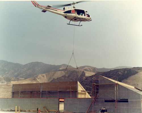 Helicopter making rooftop delivery during Malibu campus construction, 1972