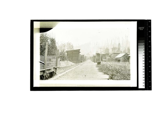 [Worker's homes, lumber stacks and a railroad car at a lumber mill]