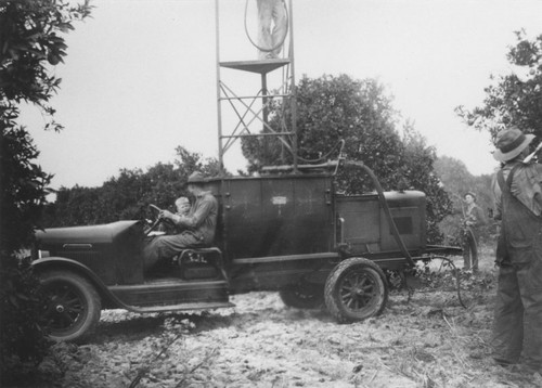 Spraying for insects in orange orchard, Orange, California, ca. 1925-1930