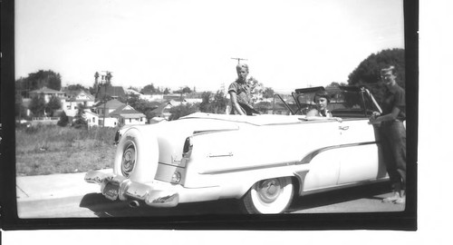 Group of young people with a light colored Lincoln Continental convertible car on Willow Street east of High Street in Sebastopol, circa 1950s