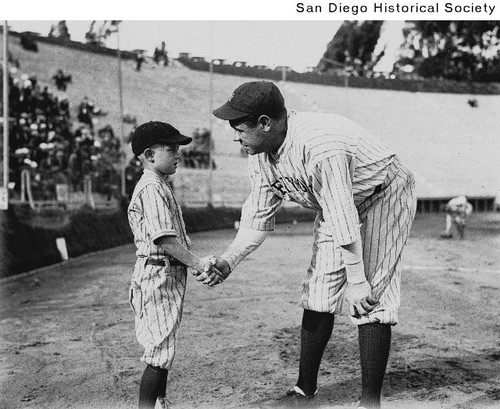 Babe Ruth in a baseball uniform shaking hands with a small boy