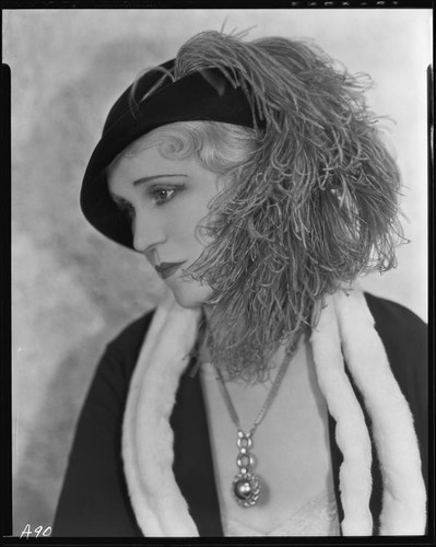Peggy Hamilton modeling a dress or coat with light fur trim and a hat trimmed with an ostrich feather, circa 1931