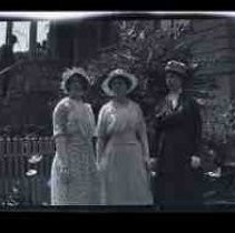 Three women standing in the front yard of a house