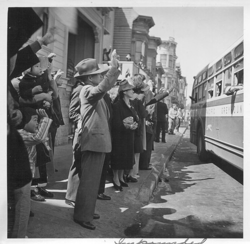 Inhabitants of the Japanese section wave farewell at the departure of their friends and neighbors whom they are soon to
