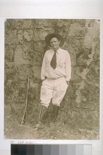 [Jack London leaning against wall with rifle beside him.]