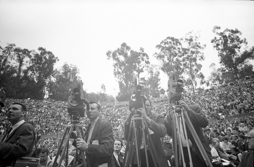 Newsmen and photographers at the Greek Theater with audience in the background