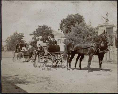 Unidentified passengers in horse drawn carriages, Sixth Street, Petaluma, California, between 1890 and 1900