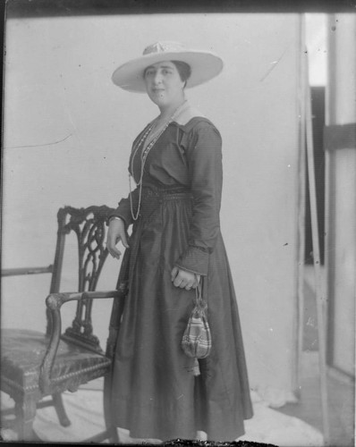Photo portrait of a woman, standing next to a chair, wearing a long dress, with jewelry and a large hat