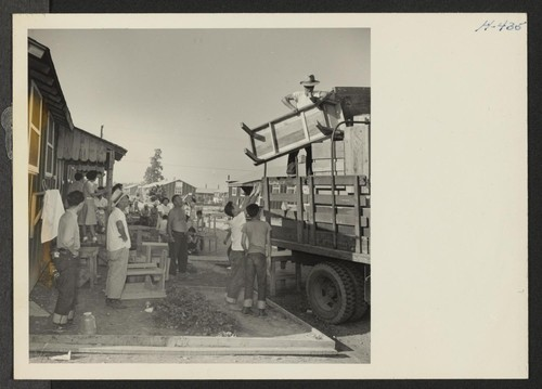 Closing of the Jerome Center, Denson, Arkansas. Scene as household furnishings were loaded in trucks for movement to the Rohwer Center. Practically all the furniture in the center is home made from plain scrap lumber salvaged from the center's sawmill. Photographer: Mace, Charles E. Denson, Arkansas