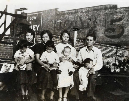 Howard Quon family sitting on a roof on Sanchez Street; pictures three women, one man and four children