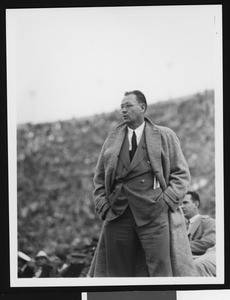University of Southern California head football coach Jeff Cravath at the UCLA-USC game, hands in pockets, standing on sidelines, shot to knees, Los Angeles Coliseum, 1944