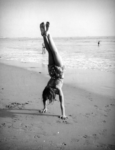 Young woman does a handstand on the beach