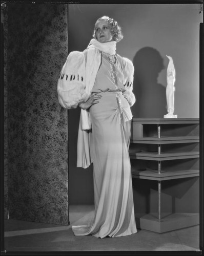 Peggy Hamilton modeling an evening gown with wide fur sleeves, 1933