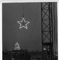 Exterior view of the California State Capitol building in the distance as the lighted Christmas Star hangs suspended from the hook of the 130' electric crane at the Capitol Towers Apartment complex between 5th and 7th, N and P Streets