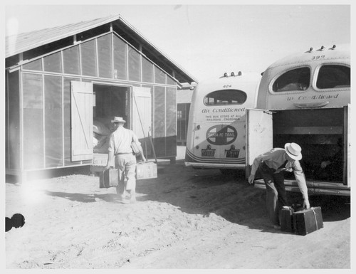 Site No. 1. Construction employees aided evacuees unload their baggage as they arrived at the relocation center.--Photographer: Clark, Fred--Poston, Arizona. 5/10/42