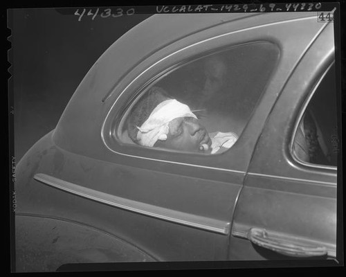 Wounded suspect, Minton R. Scott in police car after being shot by officers in Los Angeles, Calif., 1947
