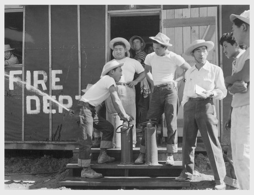 Poston, Ariz.--Evacuee firechief, Tom Nishimura, discusses Army type fire extinguisher with his staff at this War Relocation Authority center.--Photographer: Clark, Fred--Poston, Arizona. 5/25/42