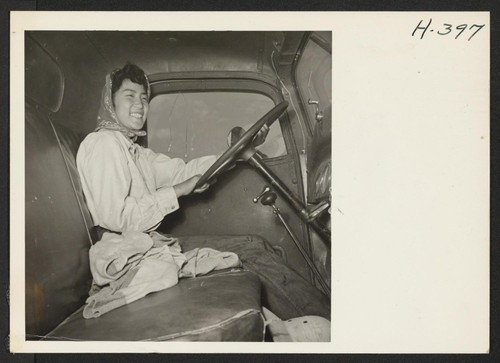 Miss Rose Tanaka, who owns and operates her own farm near Henderson, Colorado, is seen at the wheel of one