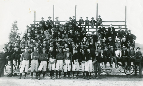 Large group of people including the Banning High School baseball team posing for photograph on bleachers