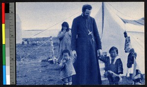 Missionary father standing with children outside of a tent, Canada, ca.1920-1940
