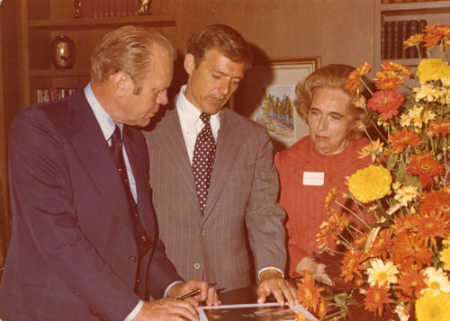 President Gerald Ford autographing photos with William S. Banowsky and Margaret Brock, 1975