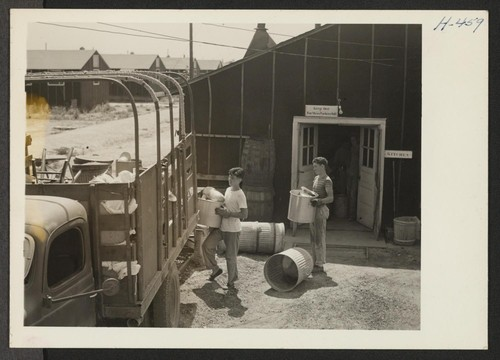 Closing of the Jerome Center, Denson, Arkansas. Local boys recruited from outside the center helped in the dismantling of the thirty-three messhalls. Here they are shown loading kitchen utensils in a truck from the messhall in block 2. Photographer: Mace, Charles E. Denson, Arkansas