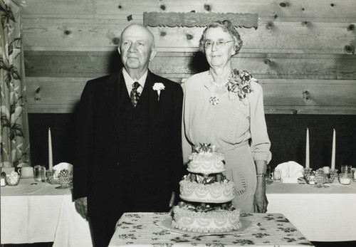 George and Emily Blank pose behind a cake for a photograph during their golden wedding anniversary celebration at the Green Mill Inn on November 1, 1949
