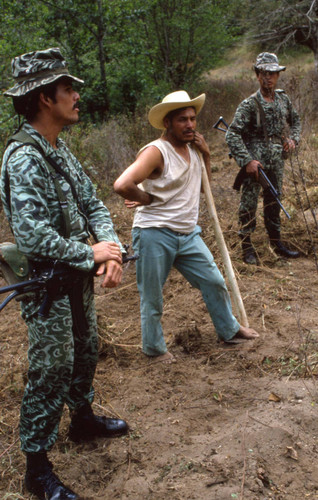 Soldiers standing with a farmer, Guatemala, 1982