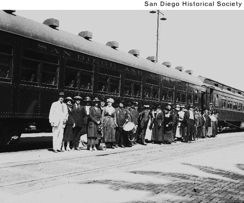 Group of people standing in front of a railroad passenger car
