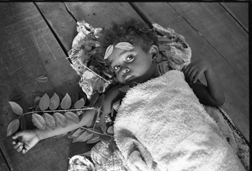 Child lies on the floor, San Basilio de Palenque, 1975