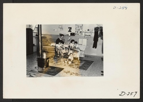 An evacuee family spends a quiet evening in their barracks. The decoration of this apartment is quite typical and shows the home made furniture, shelves, bookcases and other furniture. Photographer: Stewart, Francis Newell, California