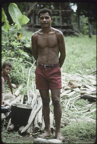 Mowaroka stands next to bucket and poles from which bark has been removed, bark (background) will be made into tapa