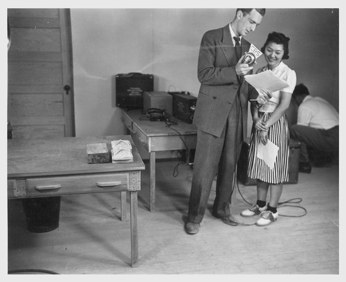 Poston, Ariz.--Florence Mori, evacuee of Japanese ancestry at this War Relocation Authority center, with Mr. Huntley of the CBS in a nationwide hookup.--Photographer: Clark, Fred--Poston, Arizona. 5/26/42