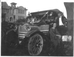 Larry Naumann and an unidentified girl, stand in front of a flag decorated car in front of Analy Union High School in 1922