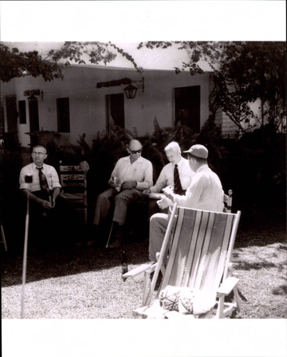 Max Poehlmann, Nathan Thompson and two unidentified men sitting in the backyard of an unidentified Sonoma County, California, home, about 1962