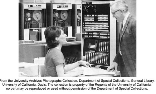 Robert Laben, University of California, Davis. Computer Center. Laben speaking with unidentified woman. Computers in background