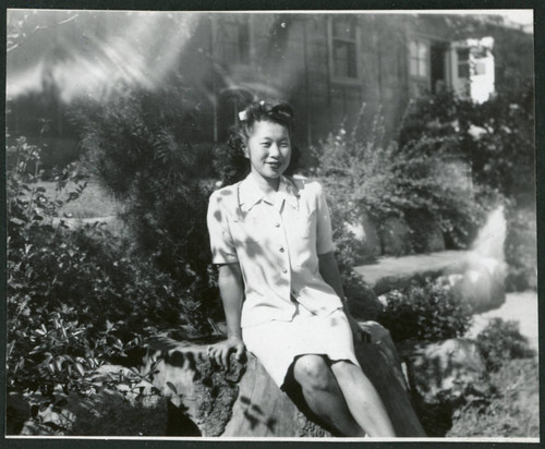 Photograph of a woman sitting on a rock in front of the Manzanar hospital