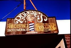Hand-painted business sign of Popeye's Haircutting and Tobacconist at 217 North Main Street, Sebastopol, California