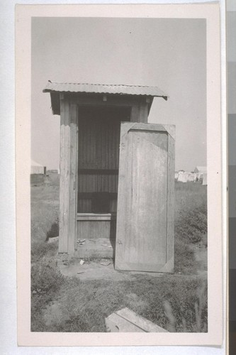 July, 1936, Kern County, Kern Lake District. One-hole privy, on one of the large scale ranches in Kern Lake District, probably the Hutcheson Ranch. Hutcheson is a millionaire living in Bakersfield. Note the filth on the floor and the door broken off