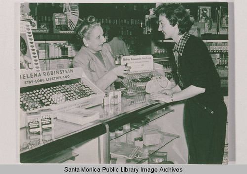 Two women at a cosmetics counter featuring Helena Rubinstein lipstick in the Bay Drug Store, Pacific Palisades, Calif