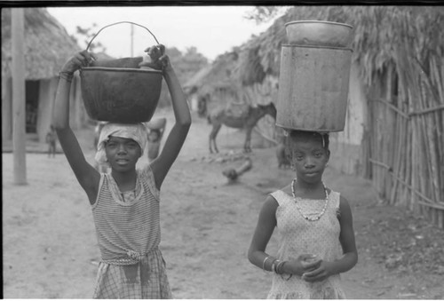 Two girls walk on the street and carry buckets on her head, San Basilio de Palenque, 1975