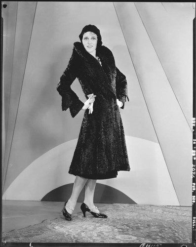 Peggy Hamilton modeling a black calf-length fur coat and a hat, 1929