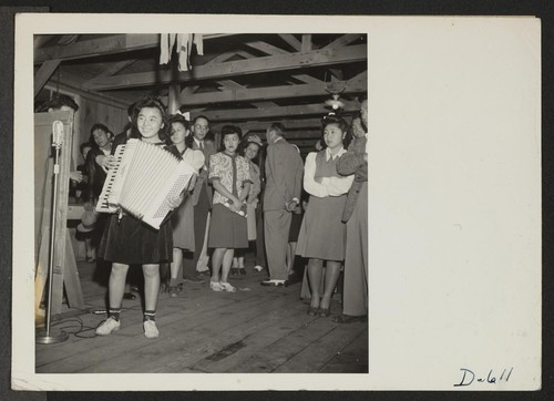 Manzanar, California--A young evacuee of Japanese ancestry entertains on an accordion at a dance given by the Girls' Recreation Committee for fellow evacuees. Photographer: Stewart, Francis Manzanar, California
